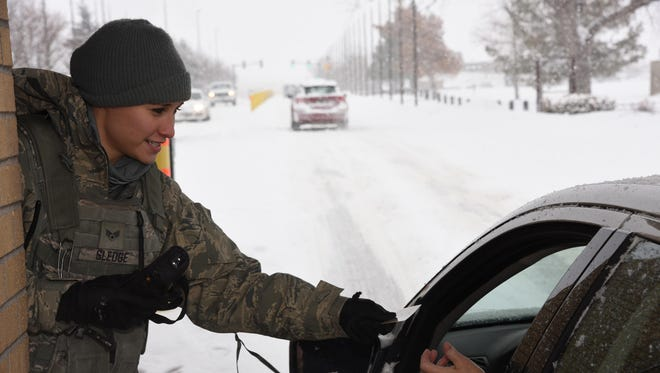 Senior Airman Kayla Sledge, 341st Security Forces Squadron member, checks military identification cards at Malmstrom Air Force Base's main gate Jan. 6. During her 12-hour shift, Sledge and her team members are responsible for security checks, vehicle searches and ensuring only eligible military and civilian personnel are allowed on the instillation.
