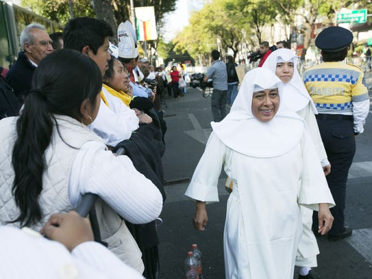 Nuns walk by as people wait for the pope's arrival.