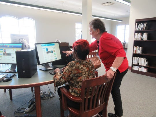 Valerie Johnson calls up the computer card catalog at the St. Lucie County Library while Bess Carnahan points to the book they looked up.