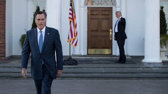 Mitt Romney walks to speak to the press as President-elect Donald Trump gives the thumbs up after their meeting at Trump International Golf Club on Nov. 19, 2016 in Bedminster Township, N.J.
