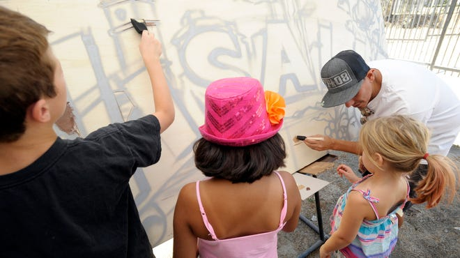 """Professional spray can artist Erik Gonzalez, right, gives tips to Tessa Stillwater, 5, from right, Atray Serrato, 9, and Everett Koontz, 10, on how to paint a community art mural during """"History in the Making,"""" a collaboration of the Tulare County Museum and the Arts Consortium Saturday at the Tulare County Museum of Farm Labor and Agriculture located in Mooney Grove Park in Visalia."""