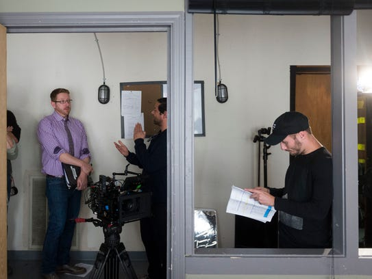 Director Jason Fisher, left, talks with photography