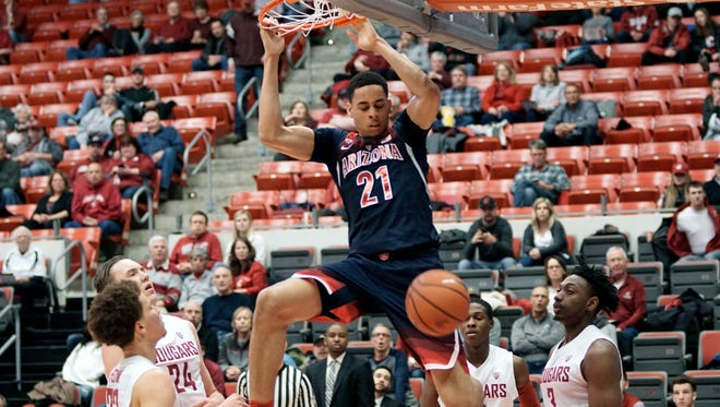 Arizona center Chance Comanche (21) hangs from the rim after a dunk against Washington State in the first half of an NCAA college basketball game, Thursday, Feb. 16, 2017, in Pullman, Wash.
