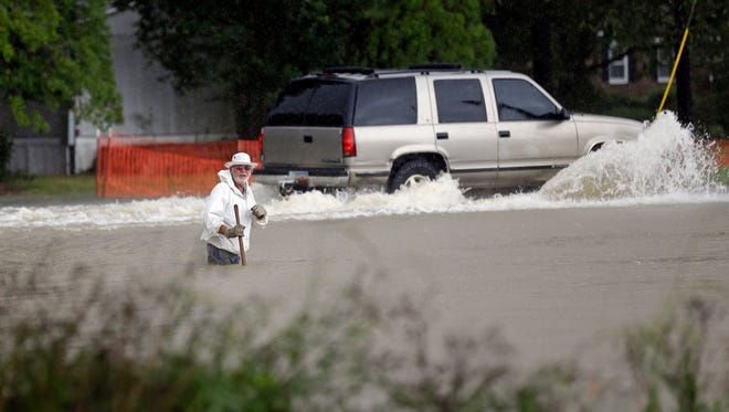Floodwaters rise as a vehicle and a man navigate flooded streets in Florence, S.C., on Sunday.