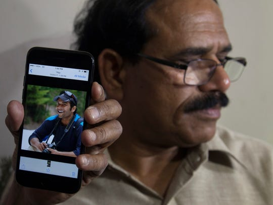 A man shows a photo of Alok Madasani, an engineer who was injured in a shooting Feb. 22, 2017, in a crowded suburban Kansas City, Kan., bar, on a mobile phone as Madasani's father, Jaganmohan Reddy, talks to the media at his home in Hyderabad, India. The shooting of two Indians in the crowded bar sent shock waves through their hometowns, and India's government rushed diplomats to monitor progress in the investigation.