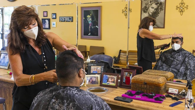 Kim Cavallaro, owner of A Shear Experience, cuts the hair of long-time customer Syed Haque Monday in West Palm Beach. Monday was the first day salons were allowed  to re-opened after being closed to slow the spread of coronavirus.