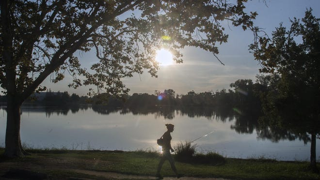 An angler makes her way to do some fishing during early evening Sept. 12 at Lodi Lake in Lodi. Headwaters Boat House at Lodi Lake will reopen Friday and Lodi Lake Beach will reopen July 1.