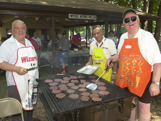 Mr. Lodato, left, mans the grill at the borough's annual