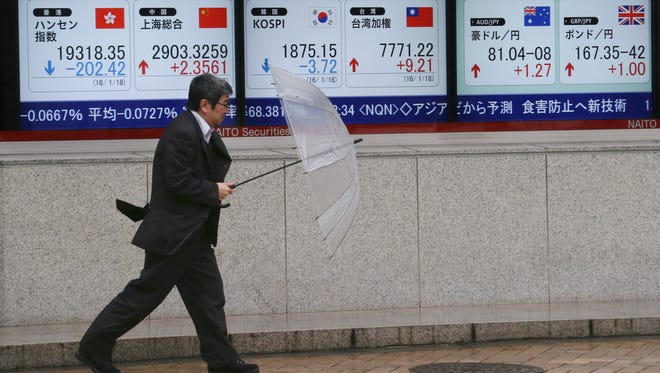A man walks by an electronic stock board of a securities firm in Tokyo, Monday, Jan. 18, 2016. Asian shares skidded lower Monday, following another dismal day on Wall Street, as investors looked ahead to Chinese economic growth figures. (AP Photo/Koji Sasahara)