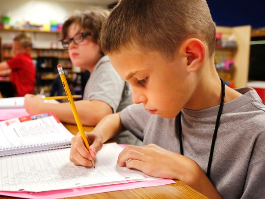 Third grade student Caleb Smith works on spelling homework during the after-school program Tuesday, August 8, 2017, at Murdock Elementary School.