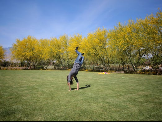 A resident of SafeHouse of the Desert does a cartwheel on the great lawn at Sunnylands Center and Gardens on Tuesday, April 8, 2014 in Rancho MIrage.