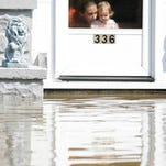 A woman and a child look out of their front door Aug. 22, 2007, at flood waters in Findlay.