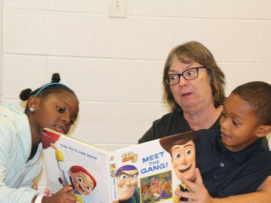 Brenda Fuller reads to two of the GYAC students on the Open House Tour.
