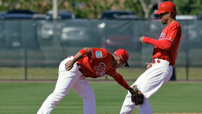 Phillies second baseman Cesar Hernandez, left, tags out Nick Williams at second base during a spring training baseball workout Friday, Feb. 26, 2016, in Clearwater, Fla. (AP Photo/Chris O'Meara)