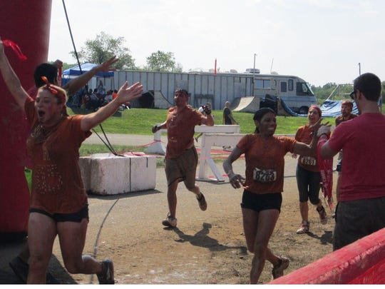 Annette Melillo, right, of North Plainfield is shown at the end of a past Rugged Maniac, collecting her medal for finishing the course.