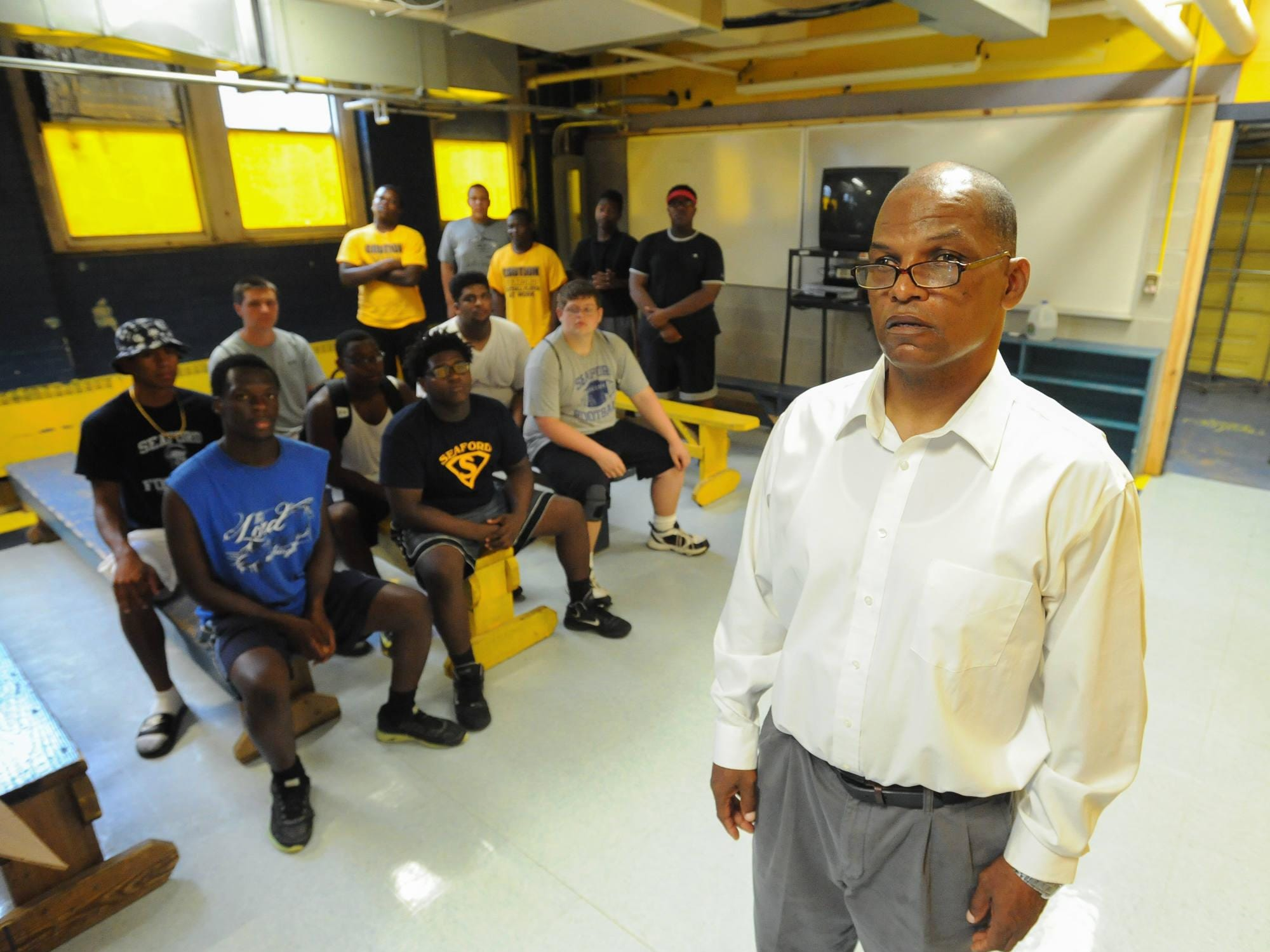 """First-year Seaford High football coach Dwayne Henry and members of his football team in """"The Pit,"""" the team's locker room at Dowd Stadium."""