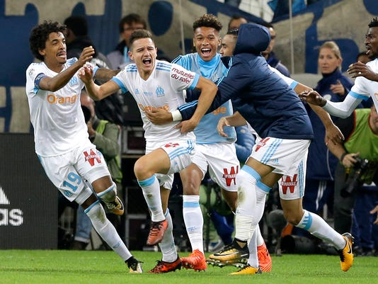 Marseille's Florian Thauvin, center, celebrates with Marseille's players after scoring during the League One soccer match between Marseille and Paris Saint-Germain, at the Velodrome stadium, in Marseille, southern France, Sunday, Oct. 22, 2017. (AP Photo/Claude Paris)