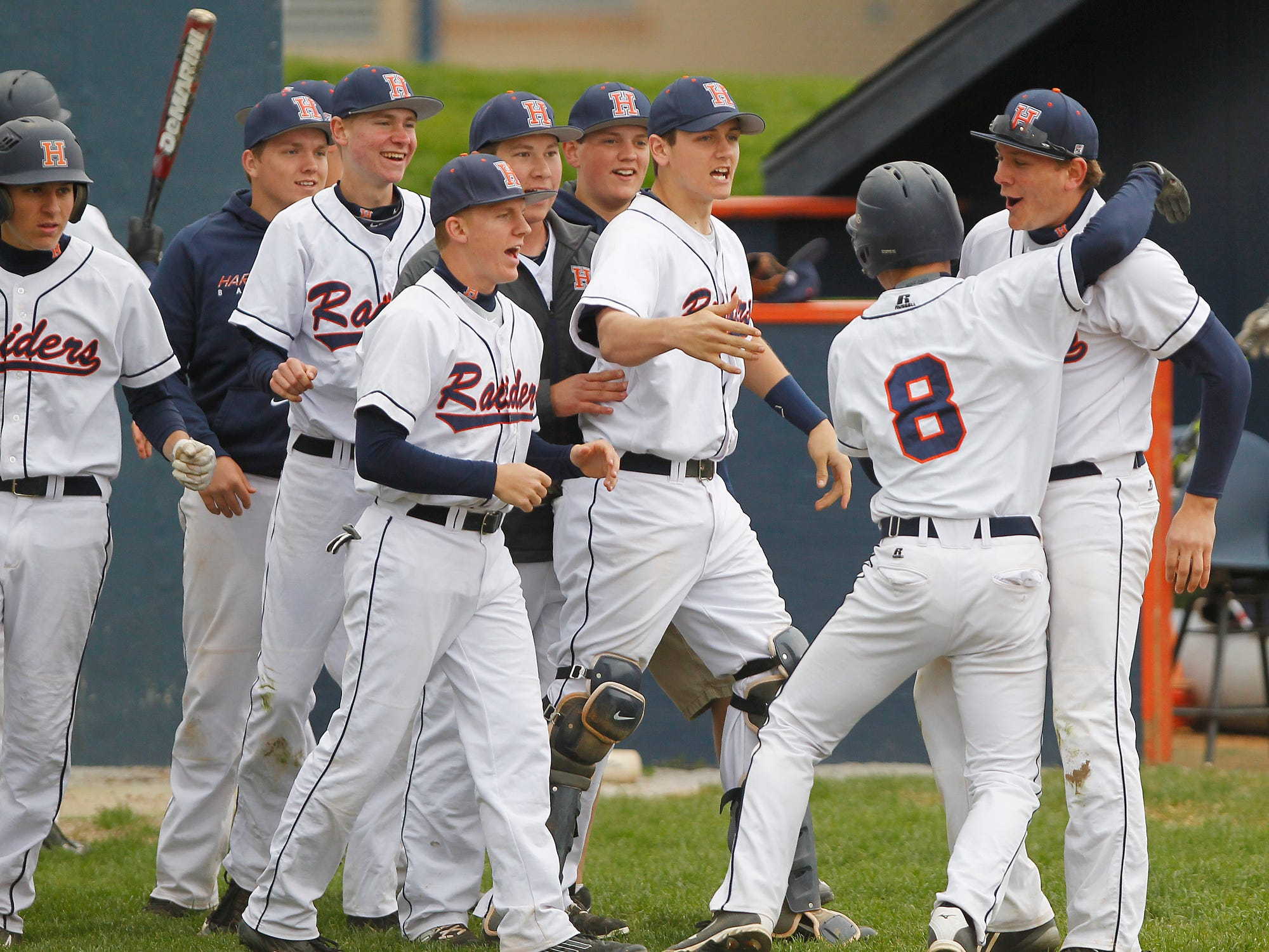 Mathew Roop (8) is greeted by his Harrison teammates after scoring on Rhett Baxter's grounder in the bottom of the sixth inning against McCutcheon.