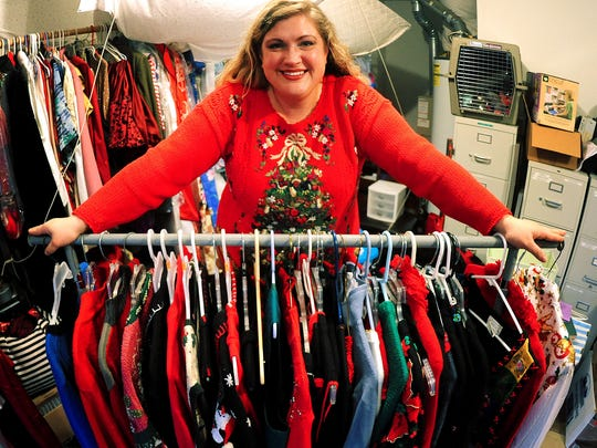 Rachel Duncan stands next to her collection of ugly holiday sweaters that she loans to her friends and students.