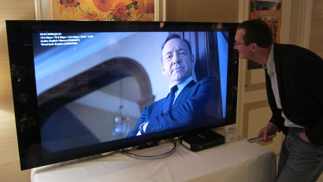 Netflix chief product officer Neil Hunt looks at an Ultra HD TV showing a 4K version of Netflix's series 'House of Cards.'
