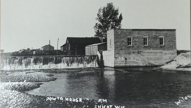 The Mishicot Dam and adjacent powerhouse as it appeared in years past. Pictured in the background is the former Twin River Co-Op building, today the site of the Mishicot Country Store.