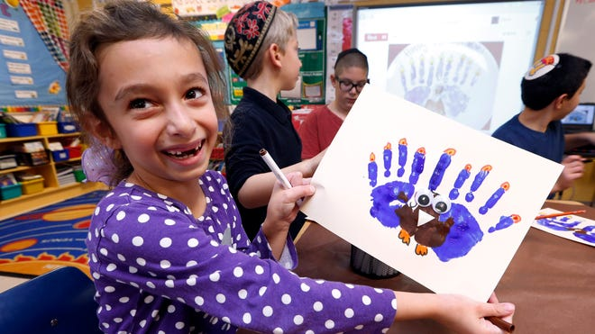 Second-grader Rozie Aronov, 7, holds up a menurkey, a paper-and-paint mashup of a menorah and turkey she created at Hillel Day School in Farmington Hills, Mich. The recent class project reflects one way for Jews in the United States to deal with a rare quirk of the calendar that overlaps Thanksgiving with the start of Hanukkah.