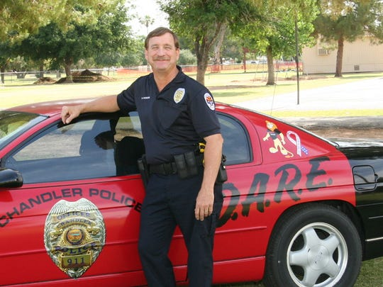 D.A.R.E. officer David Parsons poses next to his signature patrol car in Chandler.
