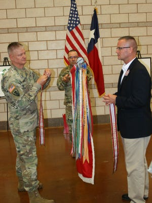 Army Col. Charles Schoening, commander of the Texas Army National Guard's 176th Engineer Brigade, left, and retired Army Col. Tim Senecaut prepare to attach battle streamers to the 111th Engineer Battalion's colors during a 100th birthday celebration at Dyess AFB on Sunday. Army Command Sgt. Maj. Jimmy Leonard, the unit's senior enlisted member, holds the colors during the ceremony.