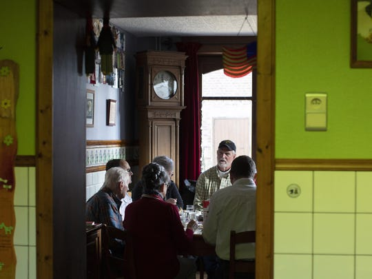 In this photo taken on Tuesday, Dec. 10, 2019, U.S. Battle of the Bulge veteran Arthur Jacobson, left, and his family have a lunch in the dining room of Remember Museum 39-45 directors Marcel and Mathilde Schmetz in Thimister-Clermont, Belgium. In the bucolic, verdant hills which were once among the worst killing grounds of WWII Marcel and Mathilde Schmetz have shared coffee and cake with countless veterans, telling stories that span generations. Veterans of the WWII Battle of the Bulge are heading back to mark, perhaps the greatest battle in U.S. military history, when 75-years ago Hitler launched a desperate attack deep through the front lines in Belgium and Luxembourg to be thwarted by U.S. forces. (AP Photo/Virginia Mayo)