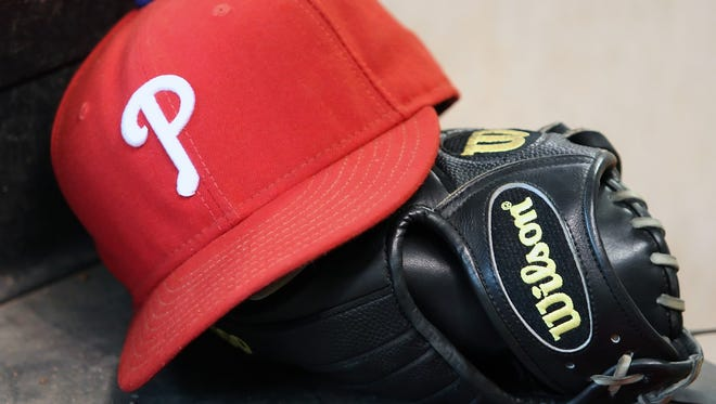 Philadelphia Phillies hat and glove in the dugout.