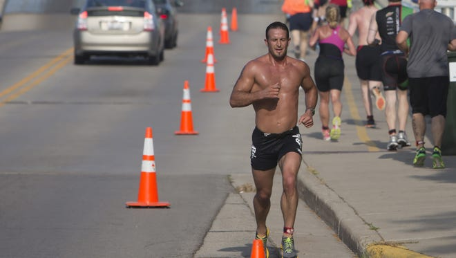 Some runners are held up by the Winneconne bridge opening with time deducted from their overall time as one Sprint competitor (bib 210) returns from his 3.1 mile run in the Winnebago County Triathlon on July 12, 2015.