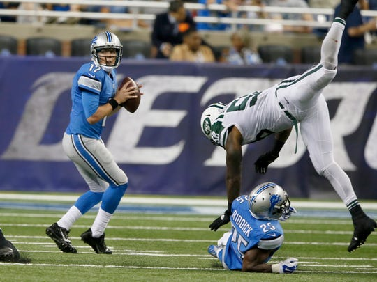 Detroit Lions quarterback Kellen Moore looking to pass as Theo Riddick trips up New York Jets pass rusher Erin Henderson in the first half of their  pre season football game on Thursday, August 13, 2015, in Detroit.