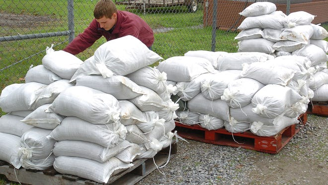 Ernest Polozola, an employee with the town of Krotz Springs, prepares sandbags Friday for residents in anticipation of  flooding conditions in areas around Krotz Springs.