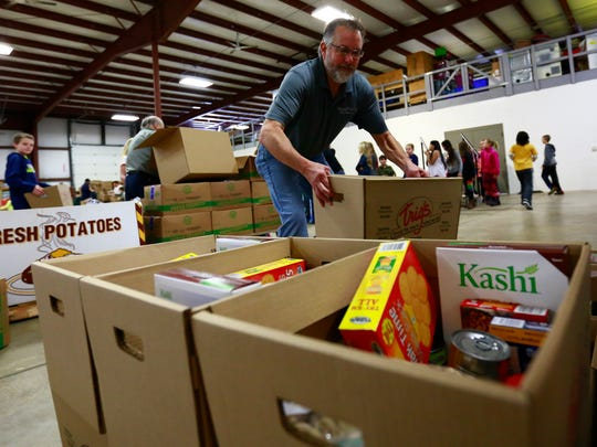 Volunteer Tim Vreeland, of Weston, helps stack up cardboard boxes of food Friday afternoon at K-tech in Weston. These boxes are packed with food by the fifth graders from Evergreen Elementary school of Rothschild.