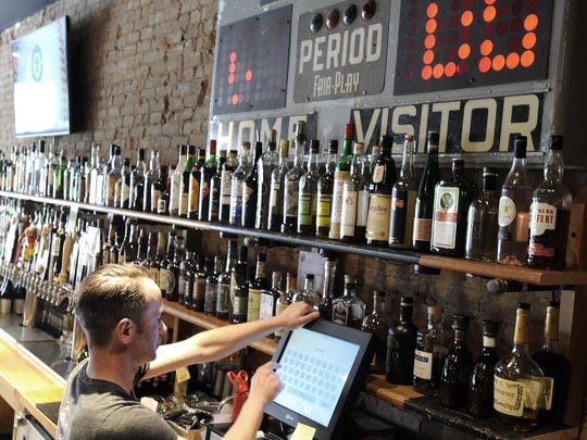 Bartender Andrew Wainio, 41, of Detroit, runs patrons'
