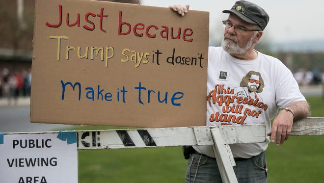 Trump protestor Keith Bentz, of Harrisburg, stands with his sign outside of the Pennsylvania Farm Show Complex & Expo Center in Harrisburg Thursday. Amanda J. Cain photo