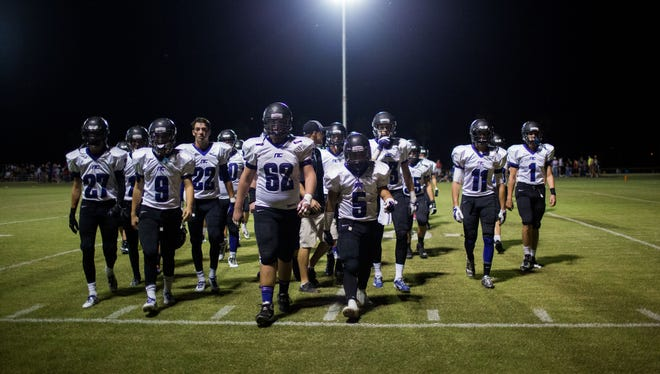 Northwest Christian football players walk off the field moments after being scored on in the first half against Arizona Lutheran on Oct. 3, 2014, in Phoenix.