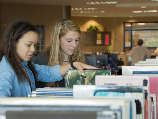 Library aides Alayna Johnson, left, and Reidan Dishaw, both Harper Creek High School juniors, arrange some used books in the library for Harper Creek's book sale May 30.