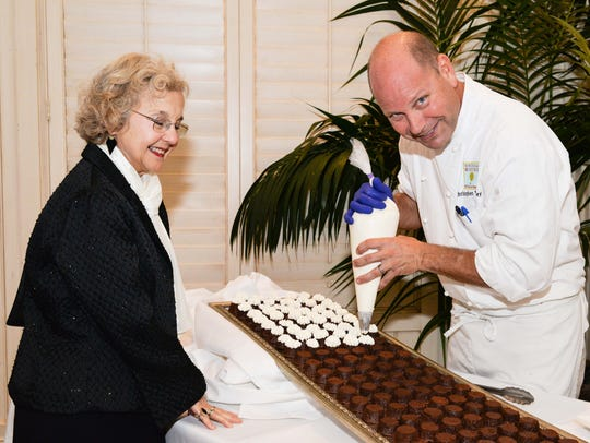 MaryAnne Egan watches as Chef Chris Bireley of Osceola Bistro adds the finishing touch to his treats at the Brothers Big Sisters of St. Lucie, Indian River and Okeechobee Counties' Chocolate, Champagne & Chefs fundraiser Oct. 30.