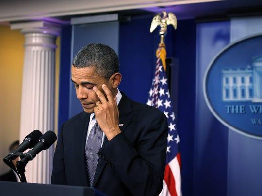 President Obama wipes tears as he makes a statement