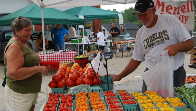 Barb Yelton purchases tomatoes from Randy Merrell of Merrell Farms at the Independence Farmers Market in 2012. Independence Farmers Market opens for the season on Saturday, April 29.
