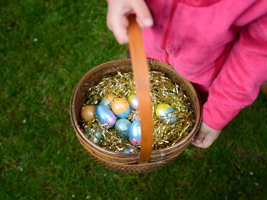Children fill their baskets with colorful eggs during
