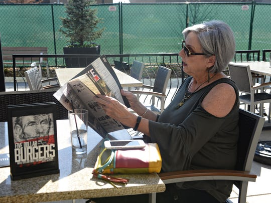 A woman looks the menu at Bar Louie at the Foothills shopping center in Midtown Fort Collins on Wednesday, April 12, 2017. Sales tax collections at Foothills continue to be strong, bucking a softening of city tax collections in the first three months of 2017.