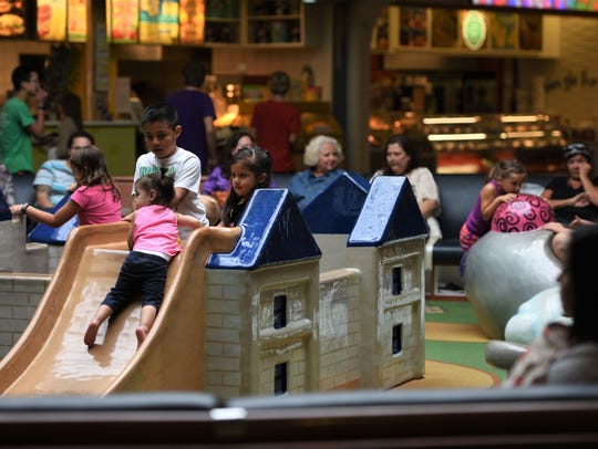 Kids play in the Empire Mall's children 's play area.