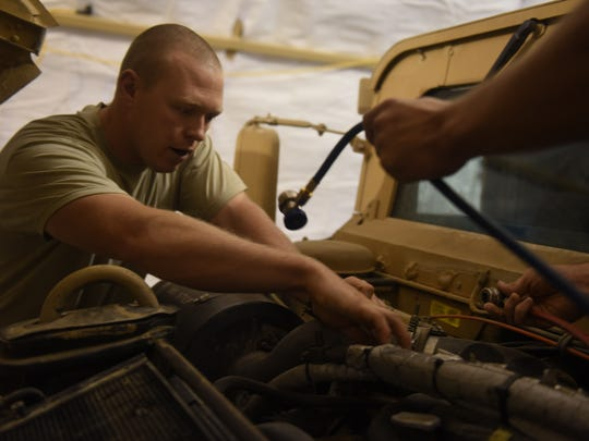 Staff Sgts. Shawn Benton, an aerospace ground equipment craftsman, and Adam Martin, a fire truck maintenance specialist, both deployed in support of Combined Joint Task Force – Operation Inherent Resolve and assigned to the 370th Air Expeditionary Advisory Group, Detachment 1, work together to charge the air conditioning system of a Humvee at Qayyarah West Airfield, Iraq, July 2, 2017. Benton often works outside of his scope to assist with vehicle maintenance and facility sustainment at the Air Force compound at Qayyarah West.