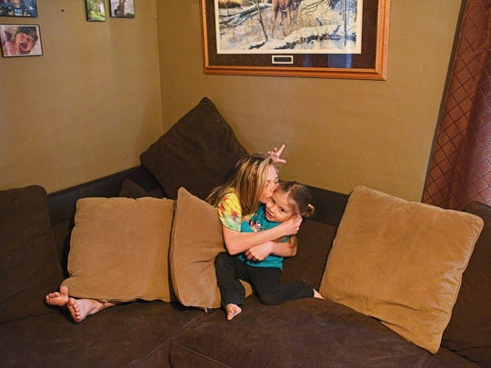 Faith Graham, 3, gets a kiss from her sister Makenzee,