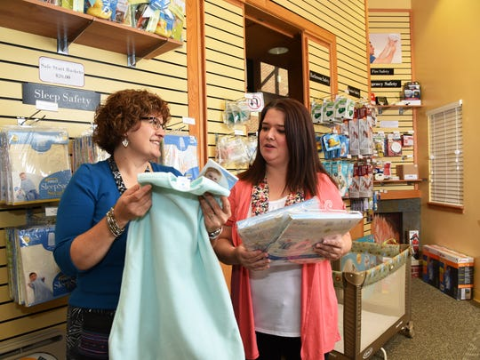 Safety Store educator Michelle Hoel, left, shows parent Becky Tamosaitis sleep sacks, used to create safe sleep environments for babies. The sleep sacks are half price at the store.