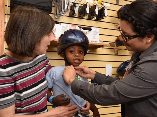 Jayden Boles tries on a bike helmet with his grandma Elizabeth Boles, left, and Safety Store educator Rosy Hyre. Bike helmets are just $6.75.
