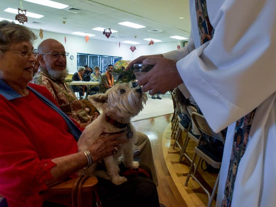 Rev. Jonathan Wickham blesses a dog Sunday, Oct. 1,