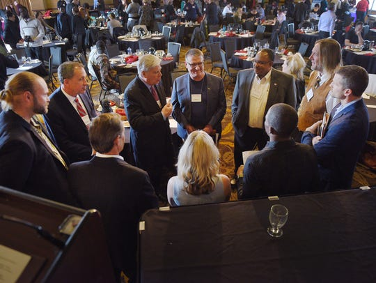 Forum moderator Jack Marsh, center, talks to mayoral